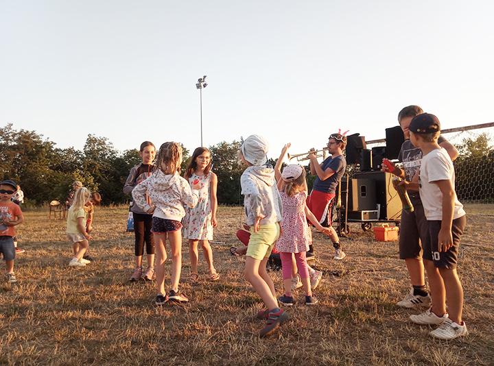 Groupe d'enfants dansant au son d'un trompettiste