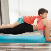 Femme faisant du yoga avec son enfant sur le dos