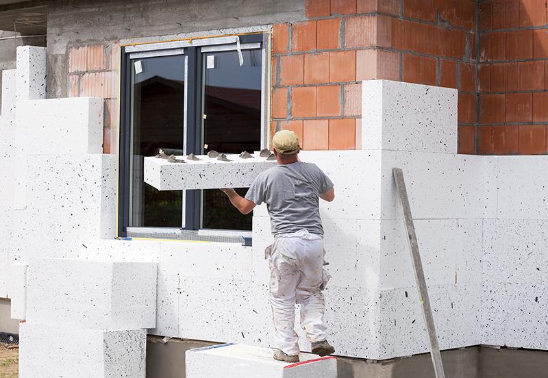 Ouvrier isolant une maison par l'extérieur