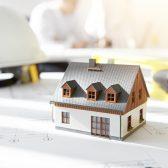 Photo d'une maison miniature posée sur des plans de construction