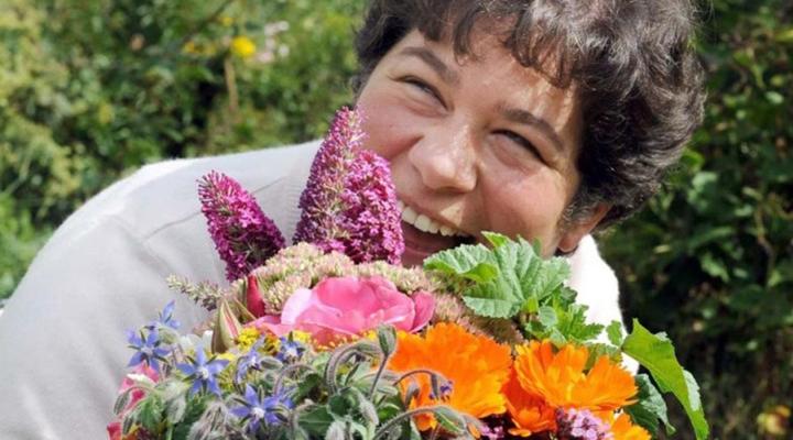 Gros plan d'une femme derrière un bouquet de fleurs