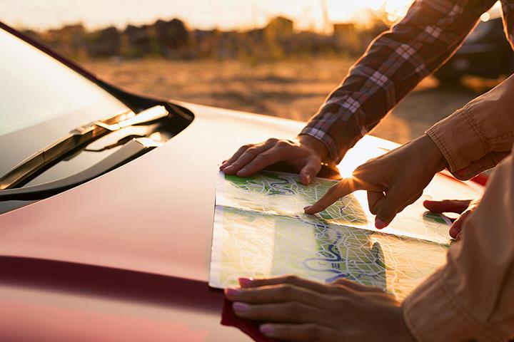 Mains avec carte sur un capot de voiture qui pointe du doigt un endroit sur une carte