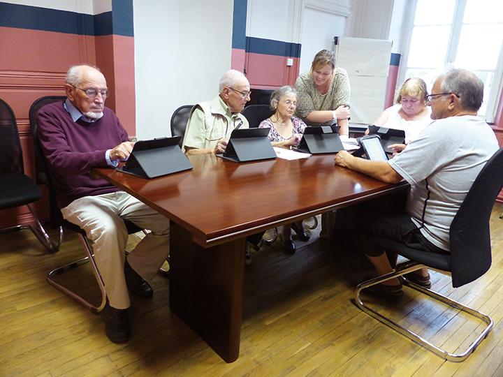 5 seniors devant des tablettes avec une animatrice debout